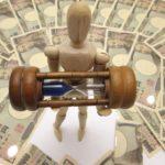 木型の人が砂時計を持ち、日本紙幣に囲まれている写真