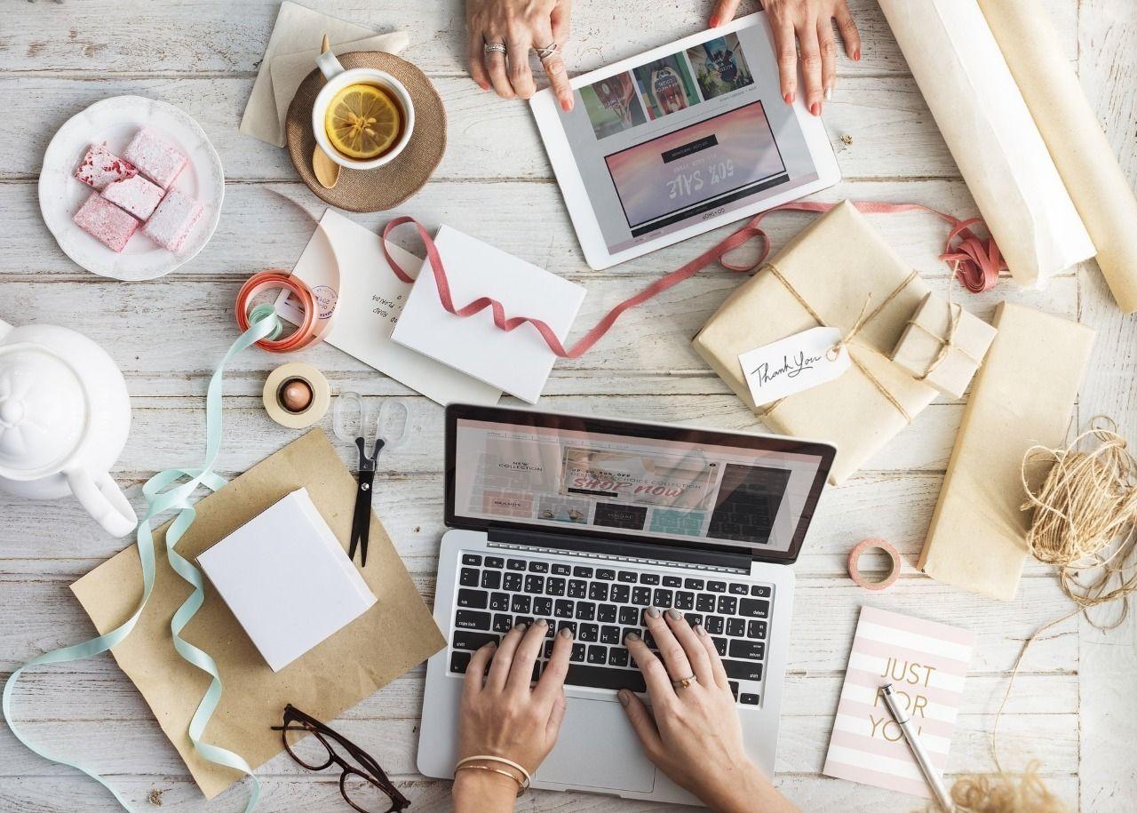白い机の上に様々な包装紙やリボンがあり、パソコンやタブレットを使って商品のパッケージングを考案している様子