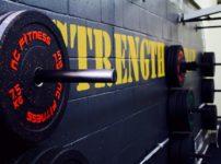 黒いブロック塀の壁に黄色の文字でストレングスと書かれた力強いトレーニングジムの一角